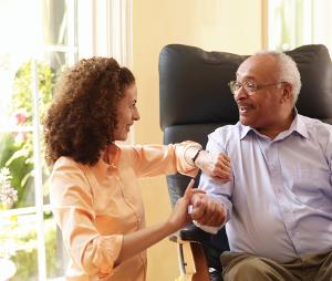 Caregiver taking man's pulse