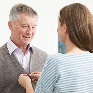 Woman helping a man button shirt