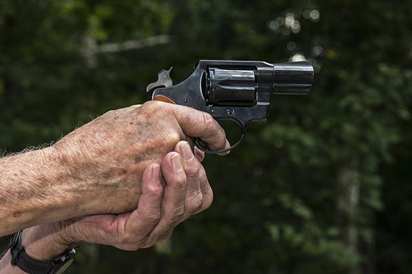 senior aiming a revolver pistol