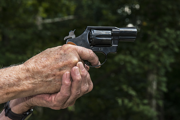 senior aiming a revolver pistol
