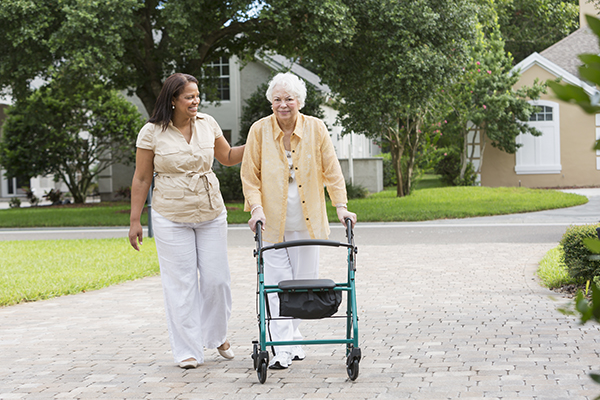caregiver assisting senior woman with walker outside