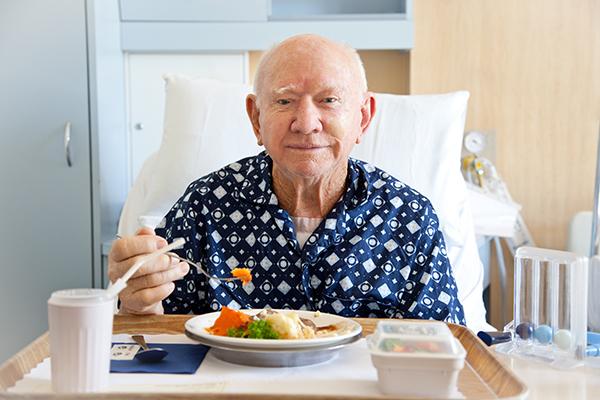 senior man eating in hospital bed