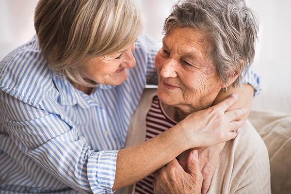 two senior women hugging