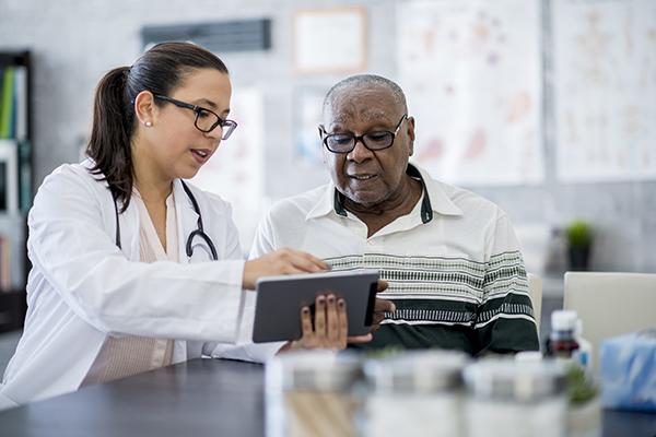 doctor explaining medication schedule to senior man