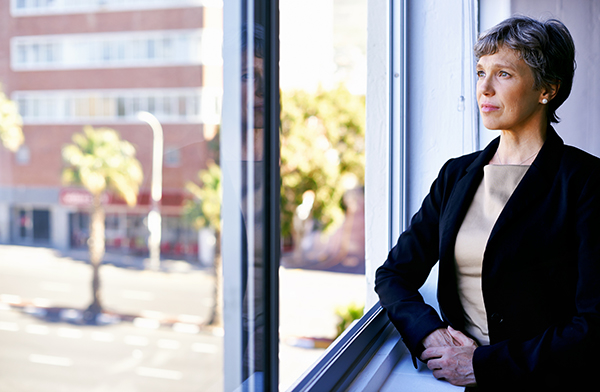 businesswoman looking out of an office window