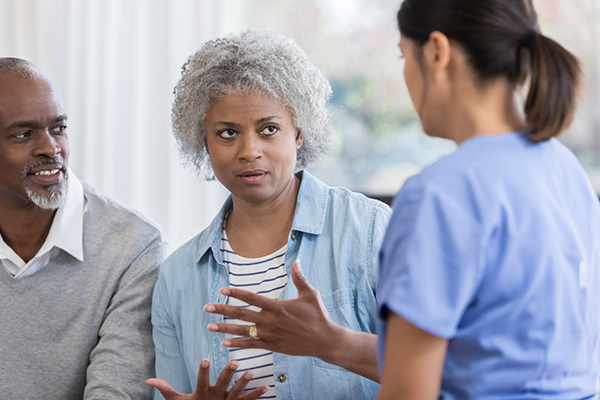 Senior woman and husband visit with doctor