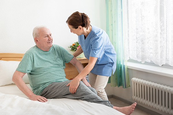 Nursing home – home caregiver helping an elderly man out of bed