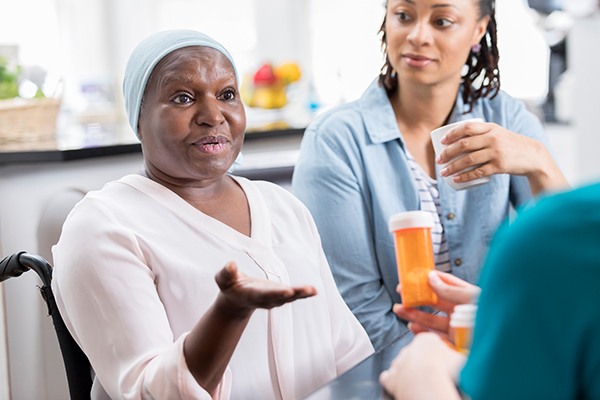 Senior female patient discusses concerns about her medication with an unrecognizable home healthcare nurse.
