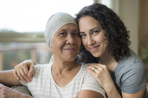 young adult female hugging her mother who has cancer