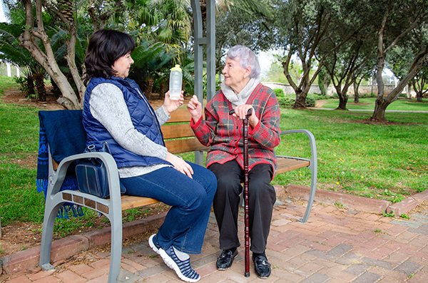 When a caregiver comes out with an older woman for a walk, she always takes a plastic bottle with water.