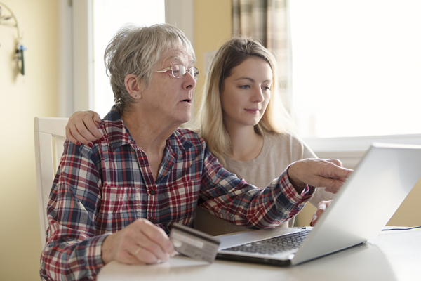 Senior woman with her daughter online purchasing together