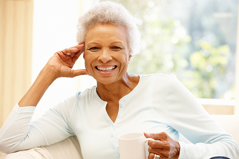 Senior woman at home drinking hot drink and smiling