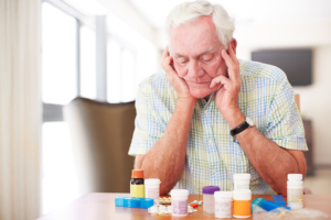Senior man sitting and looking at his medication despondantly