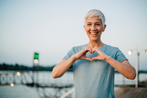 happy senior woman making a heart shape with her hands