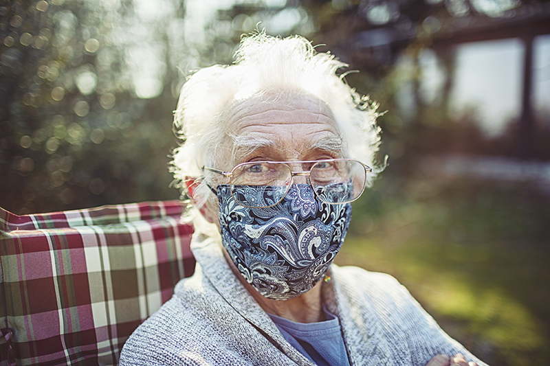 senior wears a mask to protect against viruses and bacteria