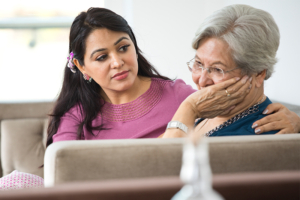 caregiver consoling senior woman