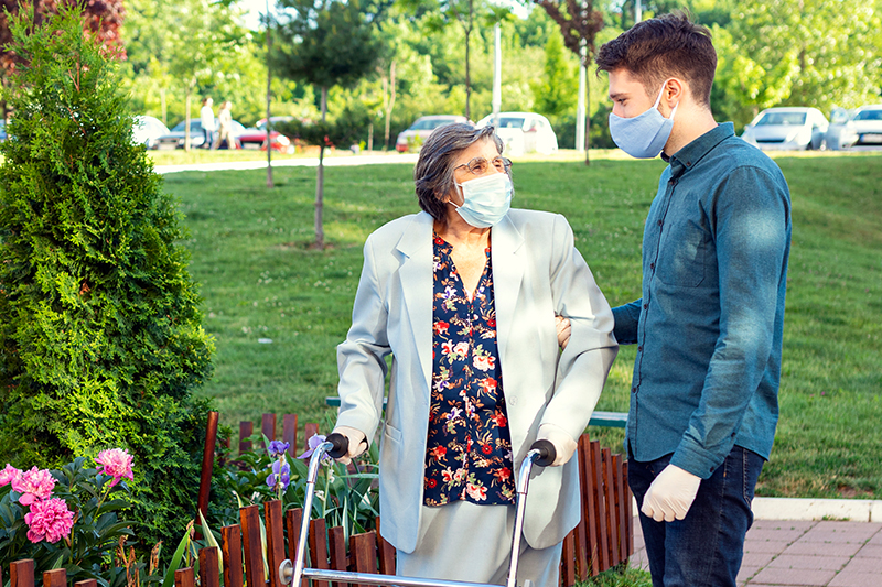senior woman outside with male caregiver
