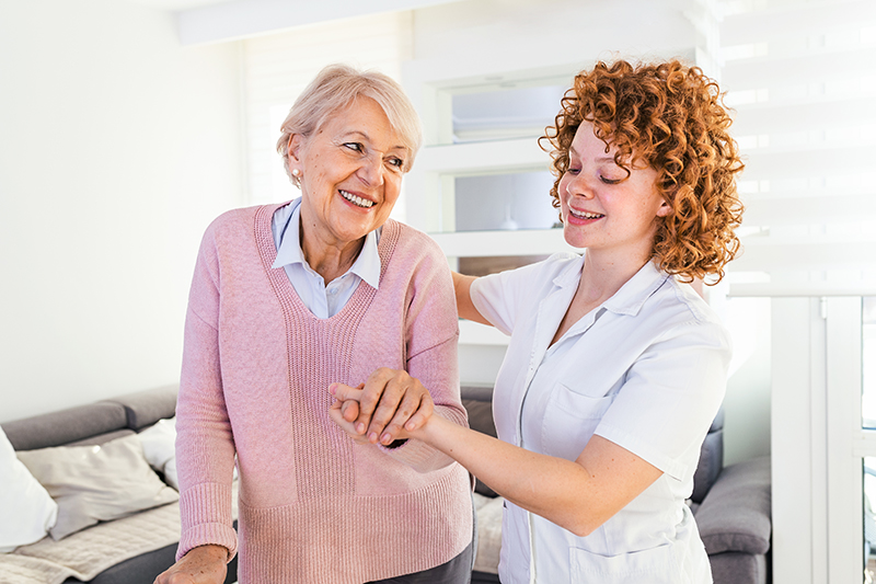 senior woman getting assistance from caregiver