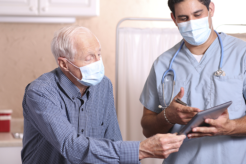 masked senior man talking with healthcare professional