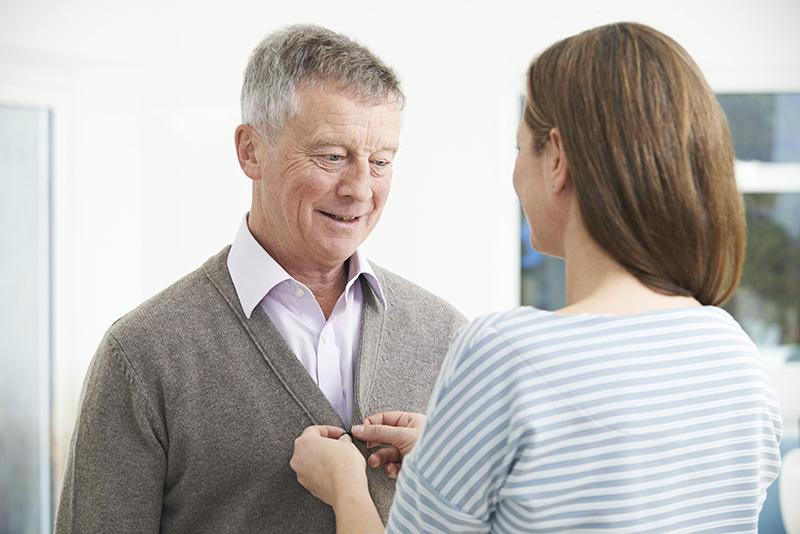 Adult Daughter Helping Senior Man To Button Cardigan