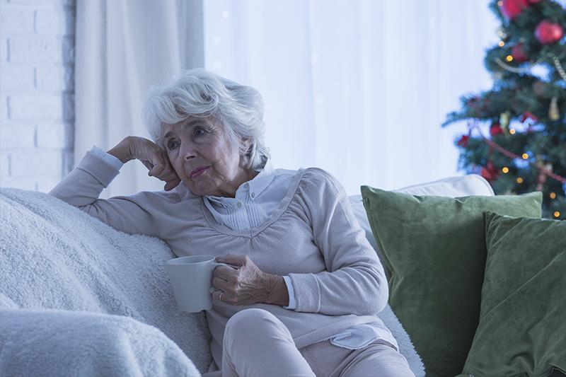 sad senior woman sitting on couch