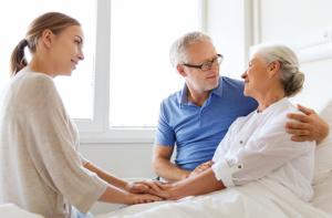 caregiver comforting senior couple
