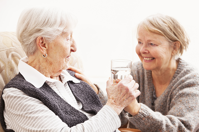 mature caregiver giving glass of water to senior woman