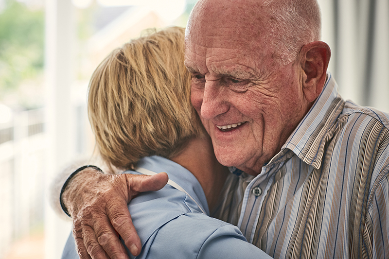 Female home carer hugging senior male patient at care home